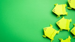 Group of origami green paper frogs